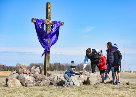 The Van Donge family brings painted rocks to the foot of a cross for Easter on Friday, April 10, at Community Reformed Church in Sioux Falls. Since Easter cannot be celebrated in person due to the pandemic, the collection of stones serves as a form of community coming together.