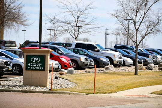 Employee cars fill the parking lot at Premier Bankcard on Friday, April 10, in Sioux Falls despite a stay at home order in place for the city during the coronavirus pandemic.