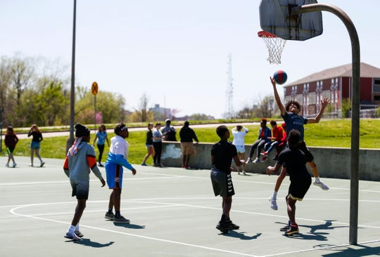 A group of teenagers shoots some hoops as another group congregates nearby at Silver Springs Park on Friday.