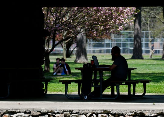 A man works on his laptop at a picnic table at Phelps Grove Park on Wednesday, April 8, 2020.