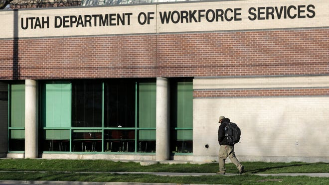 A man walks past the Utah Department of workforce Services Thursday, April 9, 2020, in Salt Lake City. More people have now applied for unemployment in Utah during the coronavirus pandemic than the previous three years combined, though the number of new claims are decreasing as the state economy reopens, officials said Thursday. (AP Photo/Rick Bowmer)