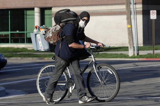 A man wears his mask as he walks in downtown Salt Lake City Thursday, April 9, 2020. The Centers for Disease Control and Prevention is now advising Americans to voluntarily wear a basic cloth or fabric face mask to help curb the spread of the new coronavirus. (AP Photo/Rick Bowmer)