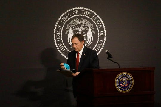 Utah Gov. Gary Herbert holds his face mask as he walks off following the daily COVID-19 media briefing at the Utah State Capitol Thursday, April 9, 2020, in Salt Lake City. (AP Photo/Rick Bowmer)