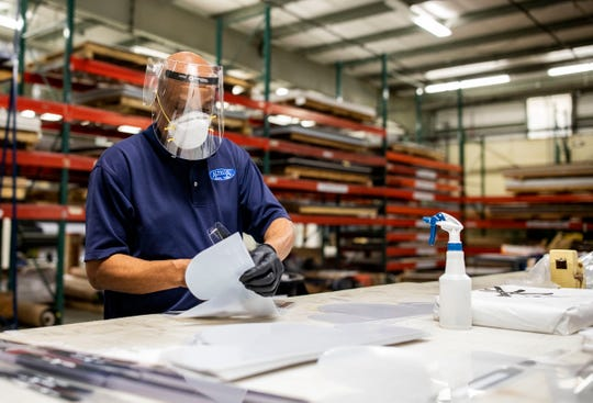 Cassidy George, a finishing specialist at Altrua Global Solutions, puts together a reusable face shield, Thursday, April 9, 2020.