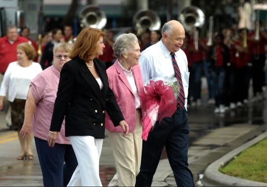 Alma Lee Loy (center) follows the parade route to the Indian River County Chamber of Commerce building with Chamber of Commerce capital campaign co-chairs Karen Diegl (left) and Jay Hart (right) November 30, 2010, in downtown Vero Beach. $1.5 million was raised to build the new chamber building which opened in early 2009. A dedication ceremony named the building after Alma Lee Loy.