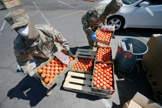 The Kelly Memorial Food Pantry and the National Guard give out boxes of onions, lettuce, broccoli, oranges, tomatoes and other goods at the food pantry Friday, April 10, in El Paso. The pantry served roughly 300 families a day before COVID-19 related layoffs. Now, it serves roughly 1,000 families a day.