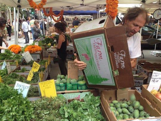 "Ojai Valley farmer Robert ""BD"" Dautch arranges fruit at his Earthtrine Farm booth in a file photo."