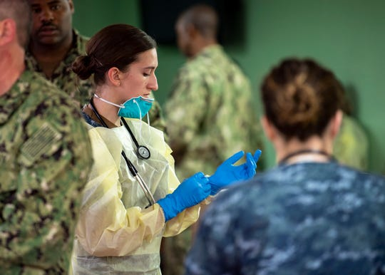 Hospital Corpsman 3rd Class Kimberly Wyss, from Ventura, dons surgical gloves aboard the hospital ship USNS Mercy on March 29.