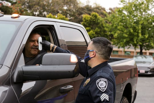 A Port Hueneme police officer uses a no-contact infrared device to take the temperature of a city employee. The department screens all officers and city employees coming to work as part of its protections against spreading the novel coronavirus.