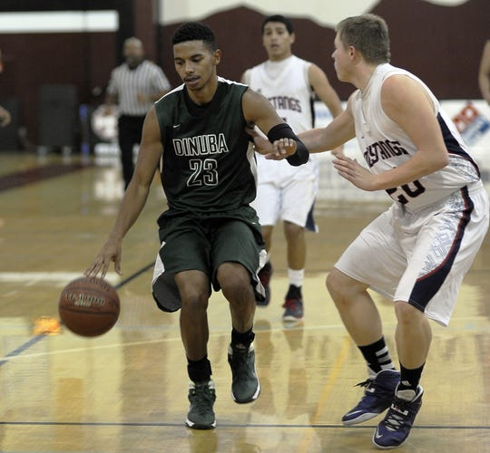 Dinuba's Marcus McMaryion (left) dribbles the ball against Tulare Western's Robin DeShazer during a first-round Polly Wilhelmsen Invitational game at Mt. Whitney High School on Monday, December 23, 2013.