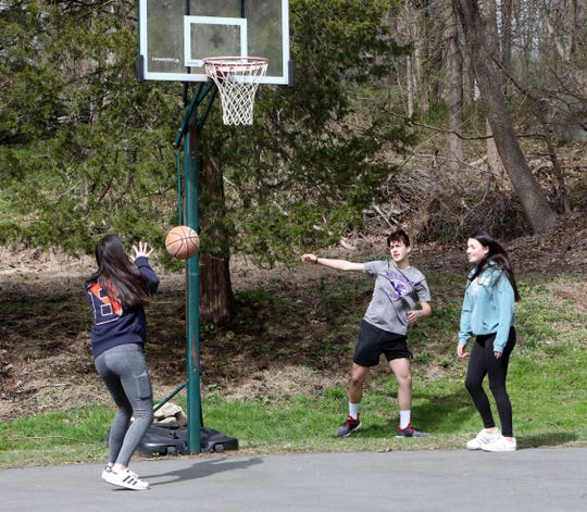 Sam Harney, 17, center, plays basketball with his 16-year-old twin sisters Caitlin, left, and Cameron outside their home in Pound Ridge, April 10, 2020. They are students at Fox Lane High School.