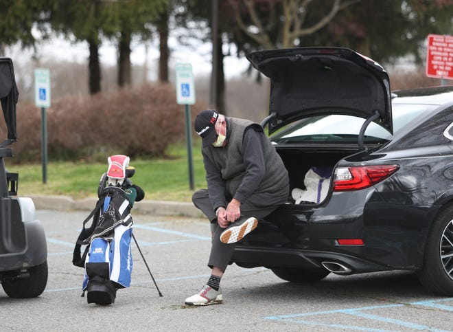 A golfer ties his shoes after completing his round of golf at Dunwoodie Golf Course in Yonkers on Friday, April 10, 2020.