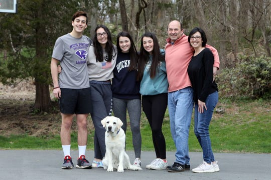 Pam and Paul Harney with their children Sam, 17, left, Stephanie, 20, 16-year-old twins Cameron and Caitlin and dog Appa outside their home in Pound Ridge, April 10, 2020. The teenagers are students at Fox Lane High School and Stephanie is home from college.
