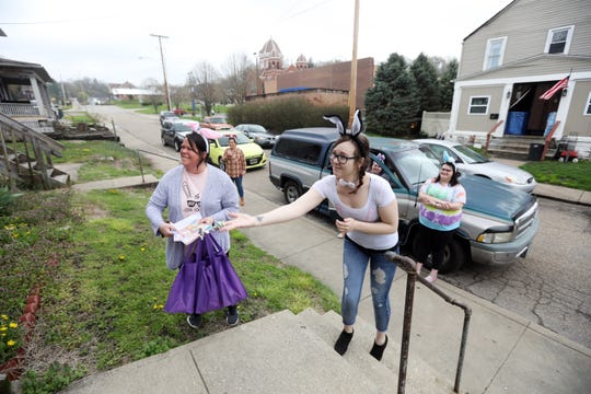Ashley Newton, right, tosses candy onto a porch on Fountain Square in Zanesville as Dessie Craig and the rest of the Eastide Community Ministries Easter Parade members get ready to spread some Easter cheer.