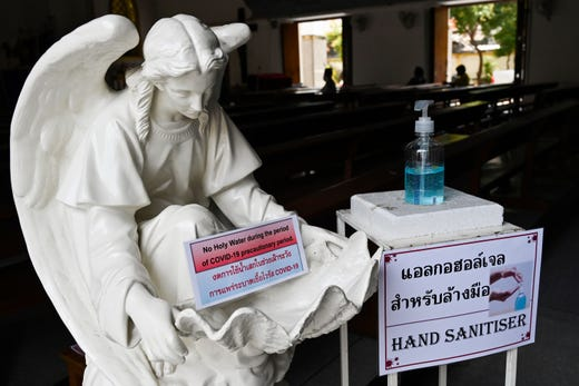 Holy water is out while hand sanitiszer is installed as part of an effort to prevent the spread of COVID-19 coronavirus at The Holy Redeemer Church during the Good Friday service in Bangkok on April 10, 2020.