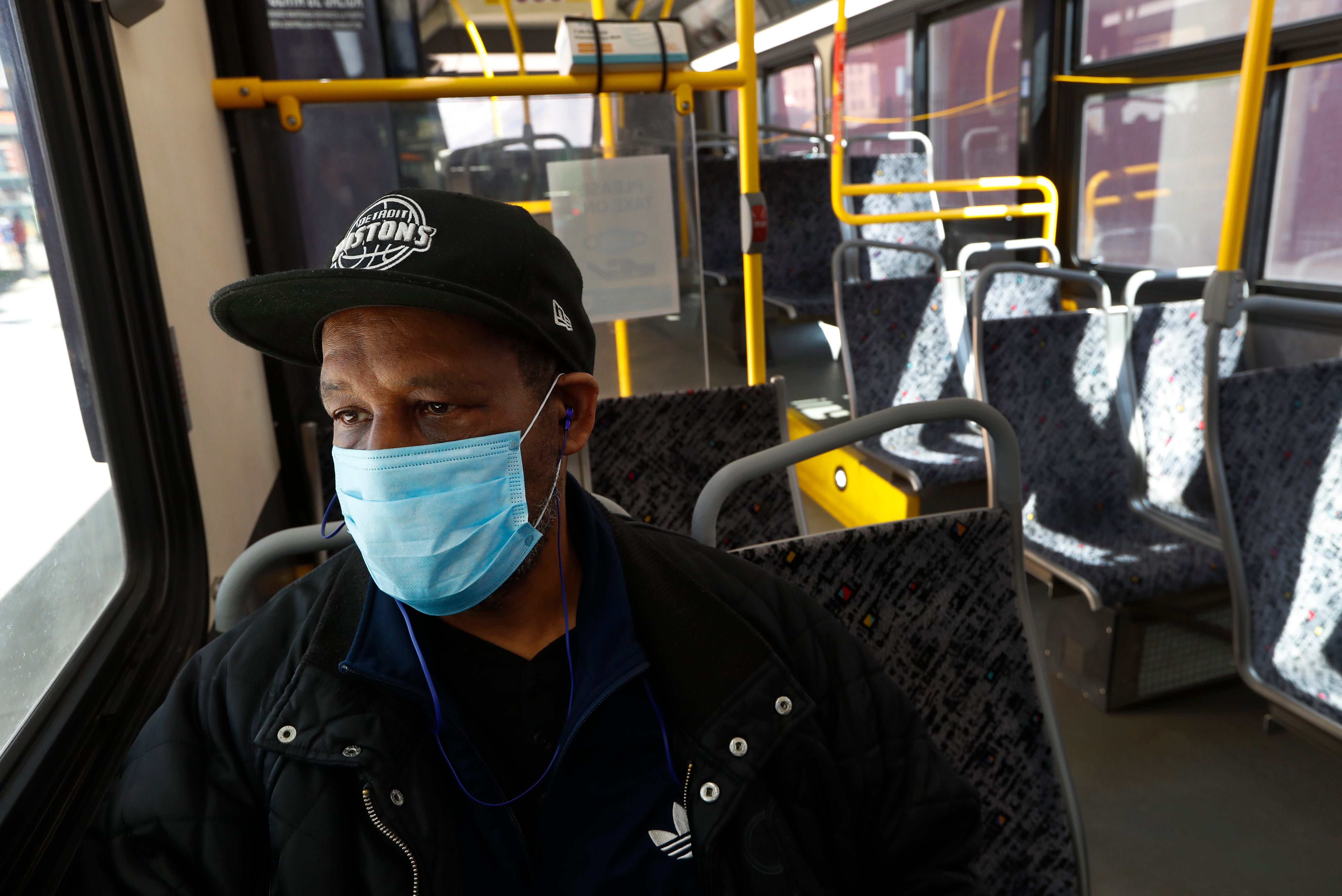 Albert Dowdell wears a protective mask on a bus during the COVID-19 outbreak in Detroit, Wednesday, April 8, 2020.