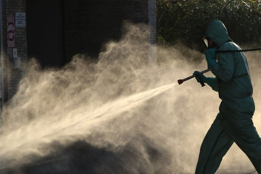 A technician sprays disinfectant along the streets of the French Riviera city of Cannes France, on April 10, 2020, on day twenty-five of a strict lockdown in France aimed at curbing the spread of the COVID-19 pandemic, caused by the novel coronavirus.