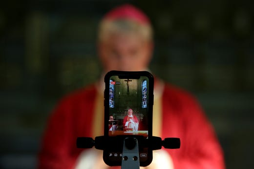 Bishop Richard Umbers is seen live-streaming during 'The Celebration of the Passion of The Lord' service at St Paul of the Cross Church on April 10, 2020 in Dulwich Hill, Australia. With religious services and congregations banned due to COVID-19 restrictions, churches are adapting their services to connect with parishioners online through email, website, live streamings and service pre-recordings.