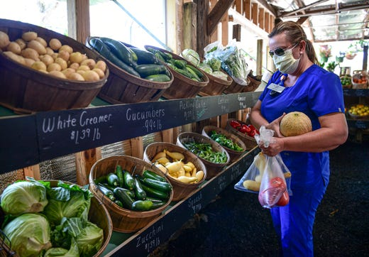 Lisa Chamblee buys produce at Concord Market in Anderson, S.C. April 9, 2020.  The market sells food and plants from local sources and is selling well according to the business.