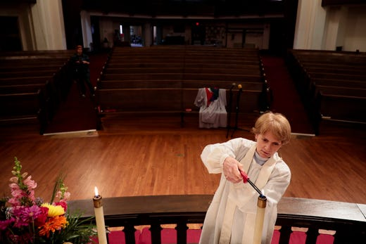 The Rev. Colleen Ogle lights candles before recording her Easter Sunday sermon inside an empty sanctuary at King Avenue United Methodist Church in Columbus, Ohio on April 10, 2020. Because of the ongoing COVID-19 pandemic, the church has canceled in-person services and instead has pre-recorded its services for congregants to watch at home.