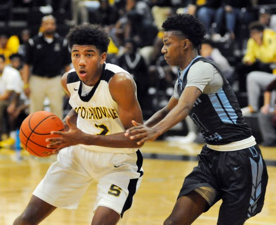 Scotlandville's Reece Beekman looks to pass the ball while guarded by Jehovah-Jireh's Roderick Dominique on Tuesday night at Scotlandville High.
