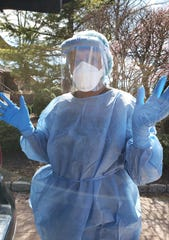 Florence Maffeu, a nurse for the Visiting Nurse Association Health Group, dons protective gear before treating a patient with coronavirus.