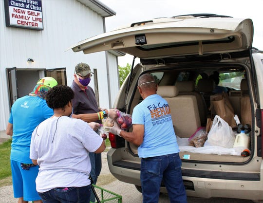 Minda Street Church of Christ members place food items in the back of an SUV at Saturday's food pantry pickup. Held once a month previously, the pantry has been open for two hours each Saturday during the coronavirus pandemic. Members wear face masks and work in limited crews.