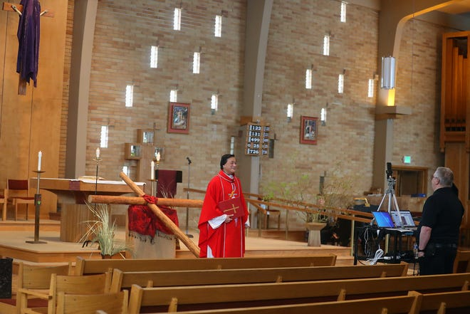 Father Phuong Hoang leads a Good Friday Mass in a nearly empty St. Gabriel Catholic Church as parish administrator Kurt Lawrence, right, live streams the event in Port Orchard on Friday.