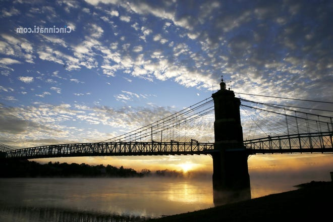 The sun breaks through the clouds near the Roebling Suspension Bridge Friday October 19, 2018.