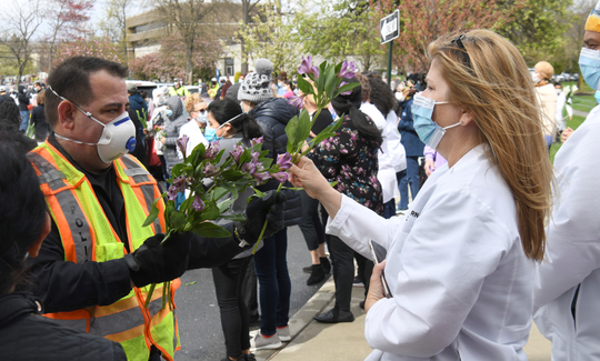 Edison Office of Emergency Management officials hand out flowers to the healthcare workers at Hackensack Meridian JFK Medical Center.