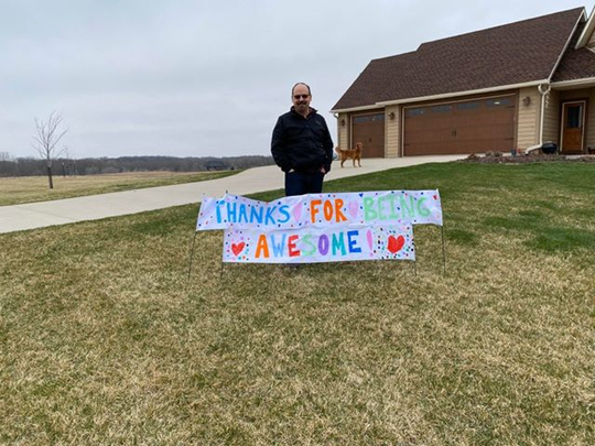 Dr. Patrick Tracy with one of the signs neighbors posted in his Ames-area yard to express their appreciation for his decision to serve as a medical fill-in in Philadelphia, the latest hot spot to emerge in the coronavirus pandemic.  (Tuesday, April 7)