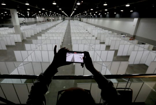 A member of the media shoots video with her iPhone of the wide-open area of Hall C filled with 600 individual rooms inside the TCF Center in Detroit, Michigan on April 1, 2020. This area along with Hall E downstairs is where patients with Coronavirus COVID-19 in Metro Detroit will be housed and treated. Members of the Michigan National Guard and the Army Corps of Engineers worked at erecting the rooms and beds for the patients.