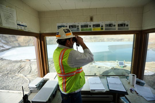 In this March 5, 2020, photo, Mark Thompson, the environmental affairs manager for Montana Resources, scans the water at the Berkeley Pit in Butte, Montana. The Trump administration is moving to scale back criminal enforcement of a century-old law protecting most American wild bird species. Thompson said it would keep up the efforts that drive away almost all birds regardless of the Trump administration's actions, mirroring pledges from some other companies and industries. (Meagan Thompson/The Montana Standard via AP)
