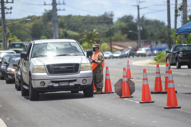 Members of the Guam National Guard stop motorists to inquire about their reasons for travel, as well as hand out COVID-19 informational fliers, on Route 1 in Asan, April 11, 2020. Motorists traveling through north and soutbound lanes on Route 1 in Asan by Calvary Chapel, Route 1 in east Hagåtña by former Shen's Furniture, Route 1 in Dededo by Lucky Supplies, and Route 8 in Barrigada by Shell gas station, will be stopped at road closures from 10 a.m. to 10 p.m., following Gov. Lou Leon Guerrero's order to deter non-essential travel.
