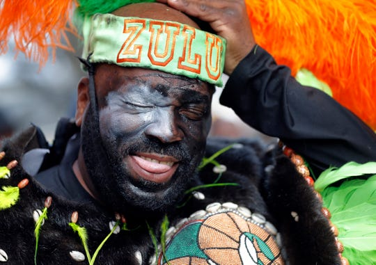FILE - In this Feb. 13, 2018, file photo, a member of the Krewe of Zulu adjusts his hat as their parade rolls on Mardi Gras day in New Orleans. In a city ravaged by the coronavirus outbreak, Zulu and its members have paid a heavy price. Several of the group's members have died from coronavirus-related complications, said Zulu President Elroy A. James. Multiple other members have tested positive. (AP Photo/Gerald Herbert, File)