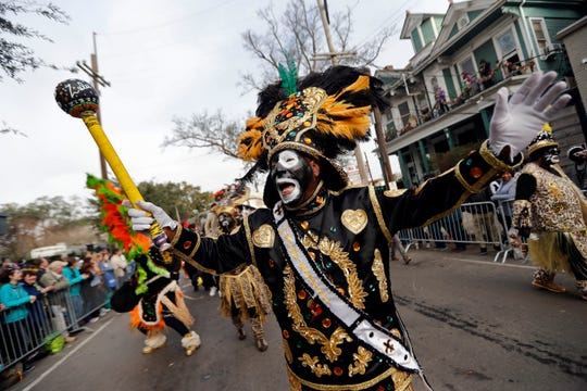 In this Feb. 13, 2018, file photo, a member of the Krewe of Zulu marches during their parade on Mardi Gras day in New Orleans. In a city ravaged by the coronavirus outbreak, Zulu and its members have paid a heavy price. Several of the group's members have died from coronavirus-related complications, said Zulu President Elroy A. James. Multiple other members have tested positive.