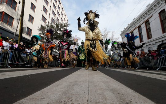 FILE - In this Feb. 13, 2018, file photo, members of the Krewe of Zulu march as their parade rolls on Mardi Gras day in New Orleans. In a city ravaged by the coronavirus outbreak, Zulu and its members have paid a heavy price. Several of the group's members have died from coronavirus-related complications, said Zulu President Elroy A. James. Multiple other members have tested positive. (AP Photo/Gerald Herbert, File)