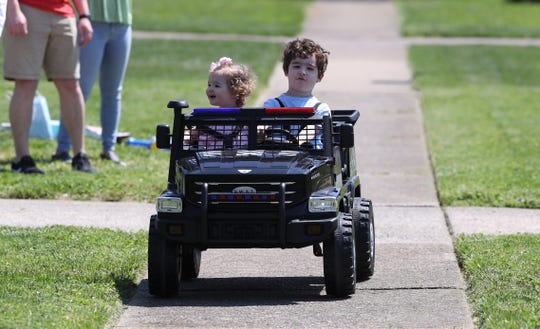 Grayson Lancaster, right, took his sister, Avery, 1, for a ride in his S.W.A.T. truck following a parade of police cars and fire trucks that rode down the street in front of his home in Louisville, Ky. on April 11, 2020.  Grayson will be 4 years old on Easter Sunday and was treated to the socially distant celebration due to the the coronavirus pandemic.  His truck was actually a Christmas present, but he enjoyed the ride for his birthday.