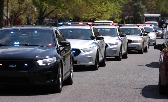 A parade of police cars and fire trucks rode down the street in front of Grayson Lancaster's home in Louisville, Ky. on April 11, 2020.  Grayson will be 4 years old on Easter Sunday and was treated to the socially distant celebration due to the the coronavirus pandemic.