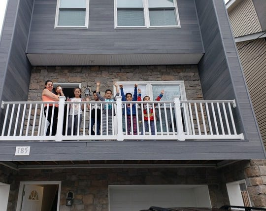 Dafani Peralta and her children on the porch of their new home in Paterson.