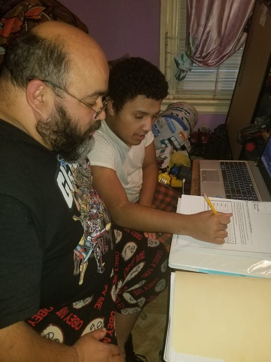 William Martinez helps his son, Angel, 13, with remote learning. April 9, 2020.