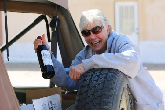 Linda Bennett holds up a bottle of one of her favorite wines outside NM Vintage, Friday, April 10, 2020.