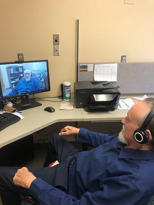 New Mexico State University counselor Louie Atencio, who works for the Aggie Health and Wellness Center's Employee Assistance Program, sits in his office. He and others NMSU counselors are now speaking with patients by phone and through Zoom.