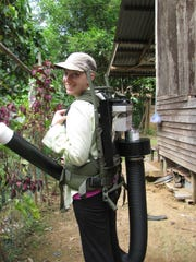 Katie Young, NMSU post-doctoral fellow, carries a vacuum used to sample blood-fed mosquitoes in Borneo.
