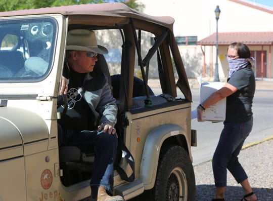 NM Vintage employee Sherry Chestnut brings a box of groceries out to Las Cruces resident Barry Bennett's Jeep on Friday April 10, 2020. Bennett and his wife Linda have been purchasing most of their groceries from NM Vintage since the stay-at-home order was established last month.