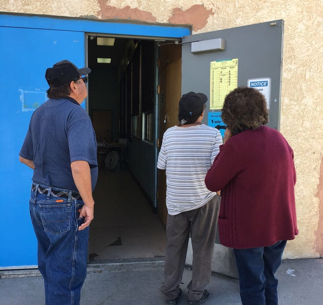 Voters look at a sample ballot for the Navajo Nation primary election on Aug. 28, 2018 at the Shiprock Chapter house.