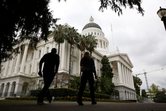 Pedestrians walk near the state Capitol in Sacramento, Calif., on March 18. California newspapers are asking the state to help their industry, as the economic crisis from the coronavirus slashes print advertising revenues, causing layoffs in an already battered industry, even as reporters are deemed essential workers during the pandemic.