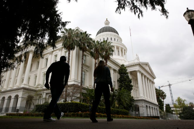 Pedestrians walk near the state Capitol in Sacramento, Calif., on March 18.