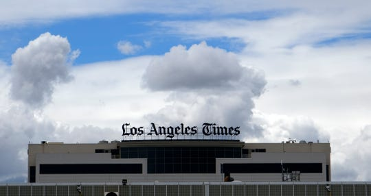 The Los Angeles Times building is seen behind a fence behind the Los Angeles International Airport, Friday, April 10, 2020. California newspapers are asking the state to help rescue their industry, as the economic crisis from the coronavirus slashes print advertising revenues, causing layoffs in an already battered industry, even as reporters are deemed essential workers during the pandemic.