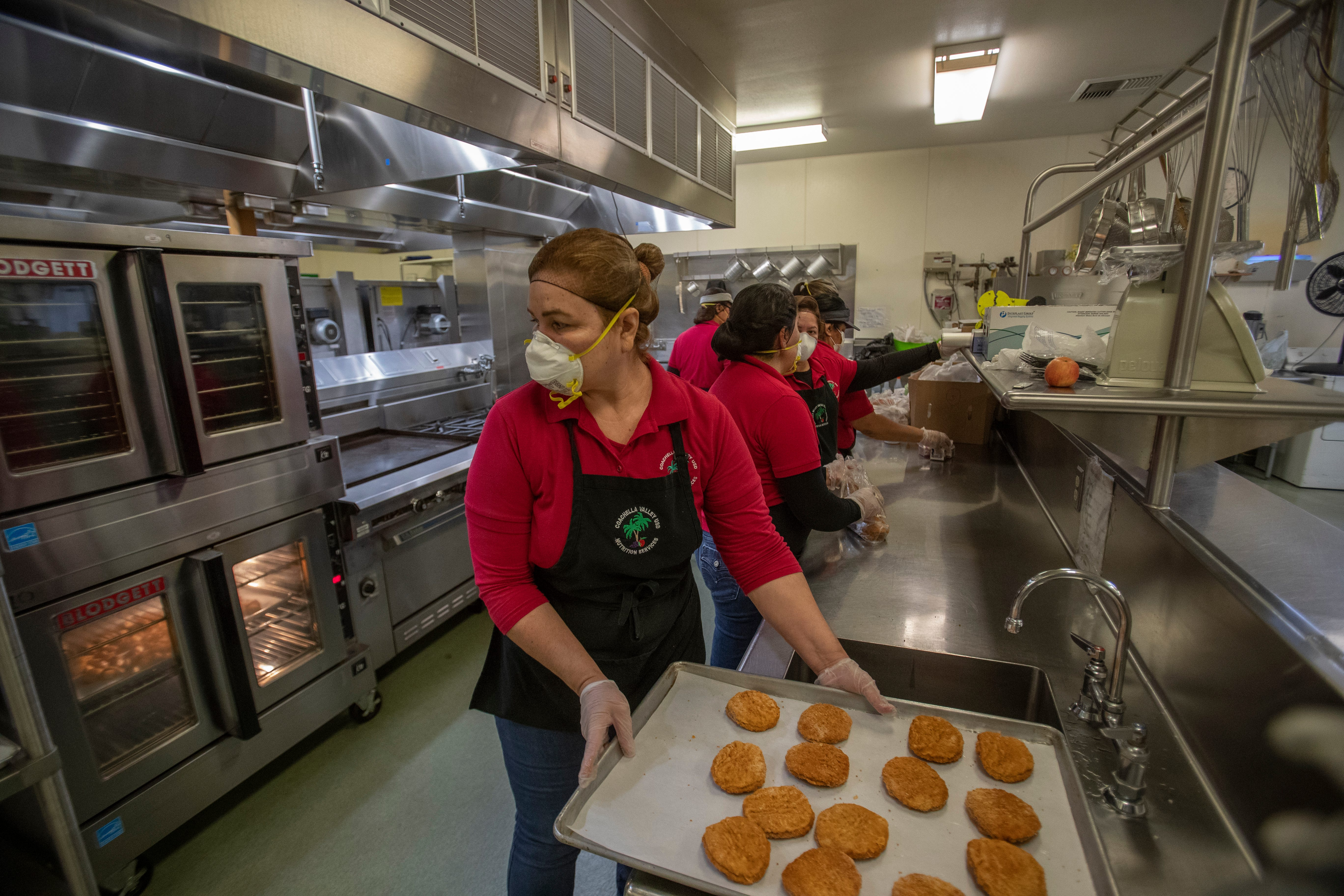 Food is prepared by Coachella Valley Unified School District employees to be load up on buses and distributed to students in the eastern Coachella Valley.